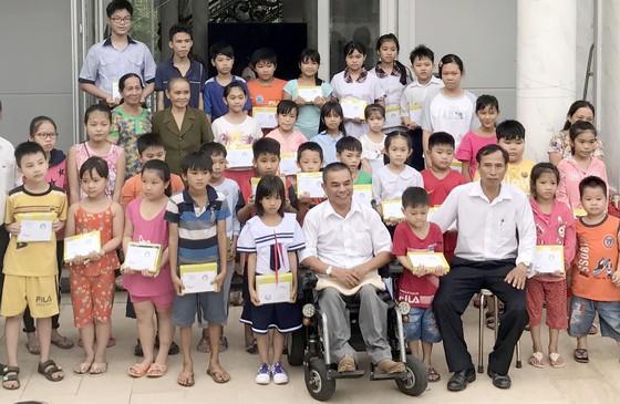Ông Trần Văn Triệu (ngồi xe lăn) trao học bổng cho học sinh nghèo